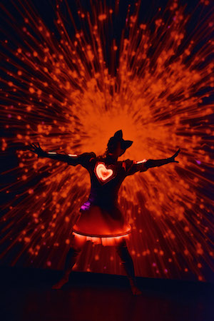 girl in red tutu lit with red exploding light