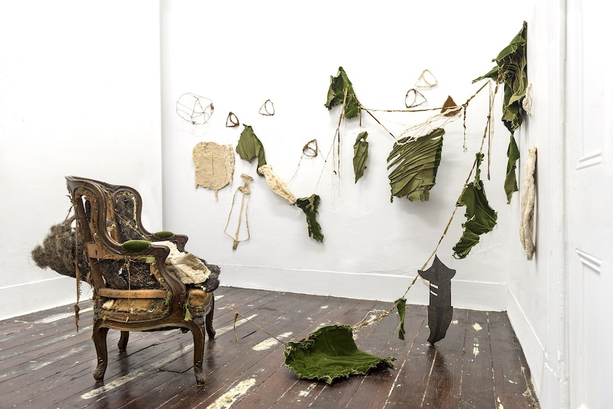 Work by Carly Lynch. An armchair is surrounded by strips of torn cloth.