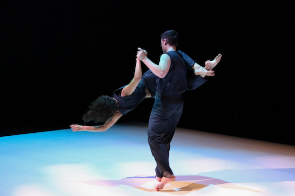 A male dancer holding a female dancer by her arm and leg