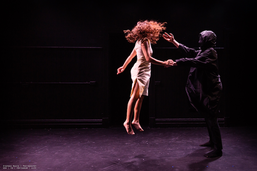 A girl jumping in the air while holding the hand of a man dressed all in black