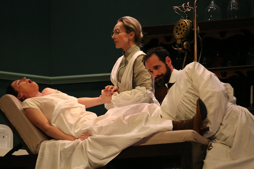 A Victorian woman lies on the bed. grasping the hand of a nurse while a doctor reaches up between her legs, his arm covered by a sheet. Her head is arched back and her mouth is open as though she is crying out.