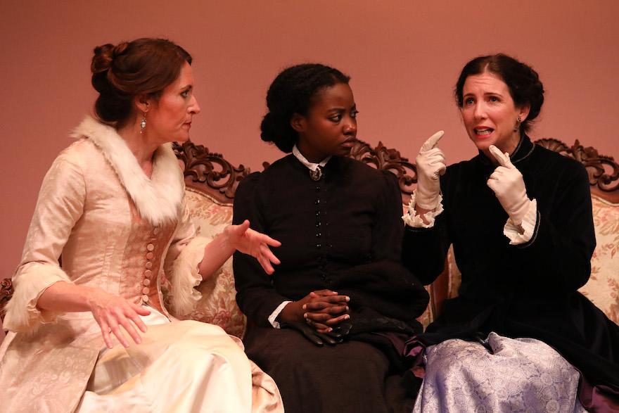 Three women talking animatedly.