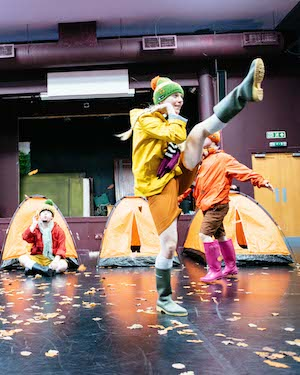 A girl dressed in a green beanie, yellow raincoat and green wellington boots, kicking one leg high in the air