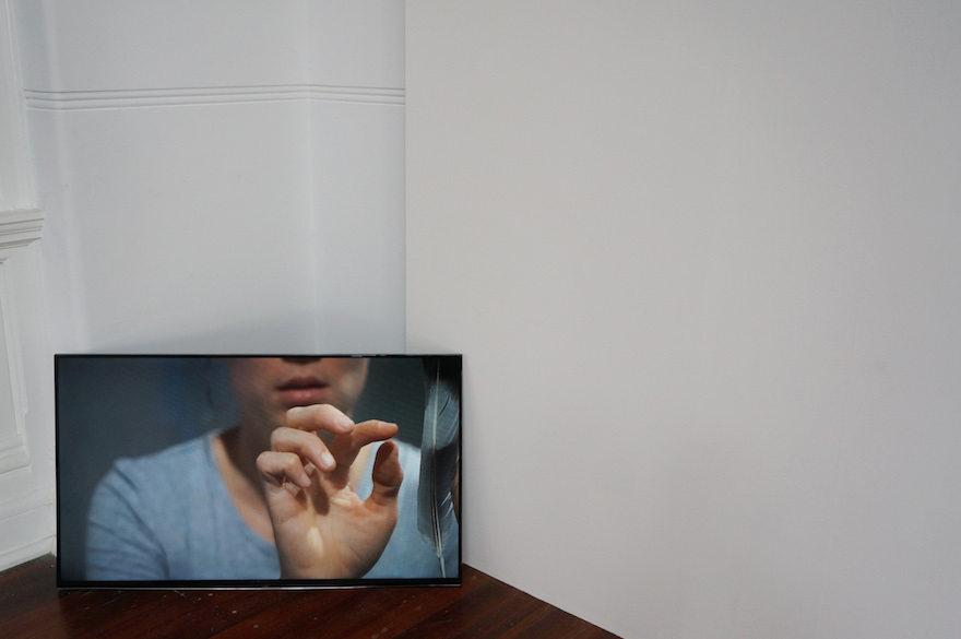 video screen with a picture of a person holding a feather