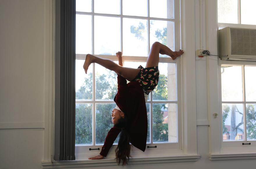 A girl upside down in a window frame.