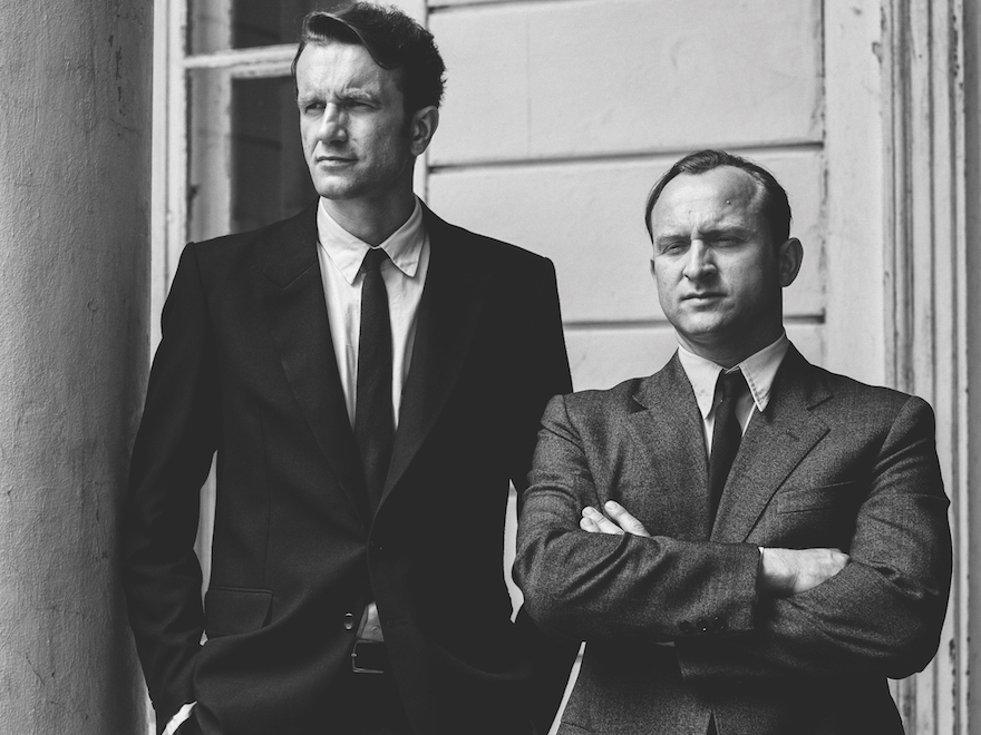 Black and white photo of two men in suits. One has his arms folded. Both gaze into the distance, not at the camera.