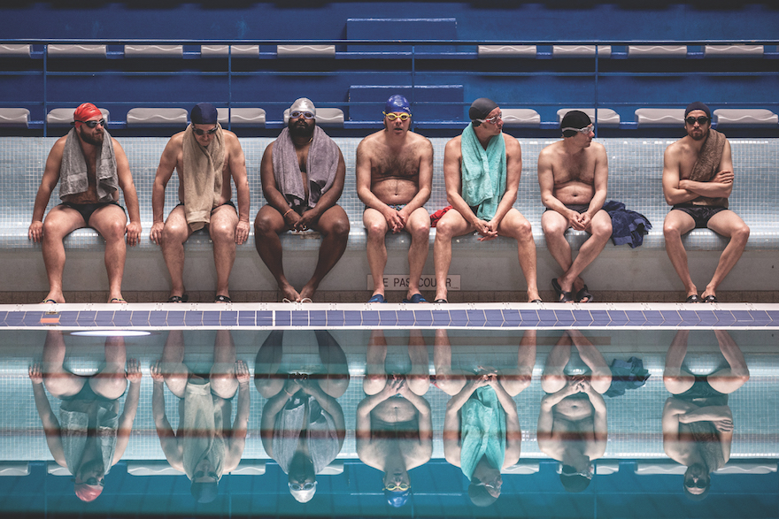 A line-up of middle aged men in bathers and swimming caps, at the edge of a swimming pool.