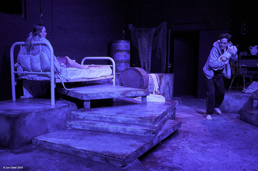 A woman on an old-fashioned steel framed bed. A man seems to be creeping towards her in the dark,