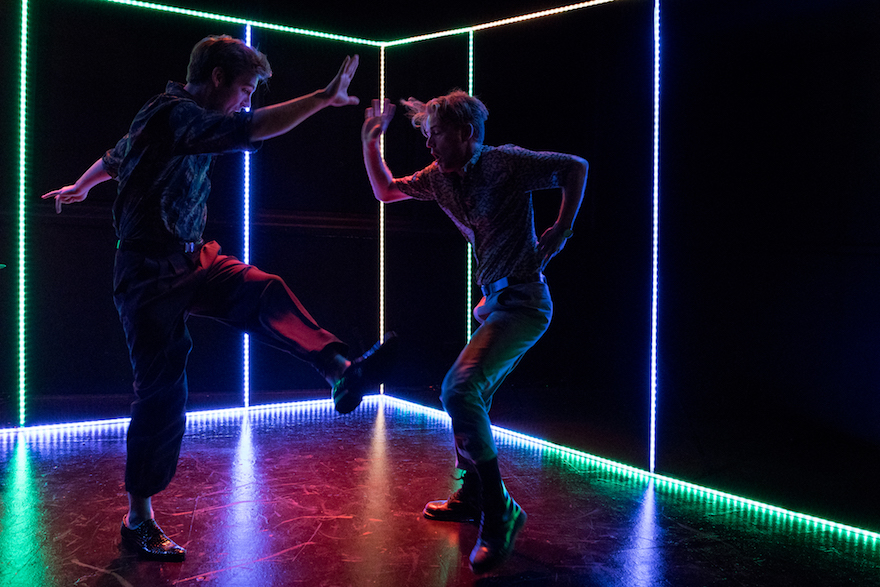 Two men dancing in the dark, lit by a frame of multicoloured LED lights.
