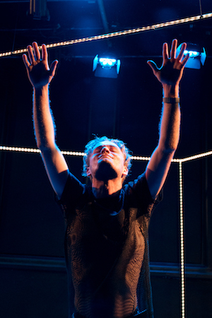 A man in a black mesh t-shirt, his arms up stretched, his head tipped back as though in ecstasy