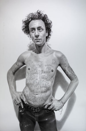 A man, naked from the waist up, decorated with tattoos
