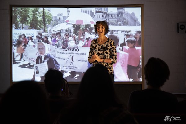 A woman smiling, standing in front of a projection of film footage of women at a protest.