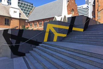 An artwork of yellow and black geometric lines on a concrete wall next to a staircase.