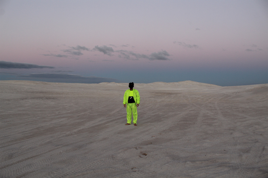 A person dressed in hi-res gear, in a desert, at sunset