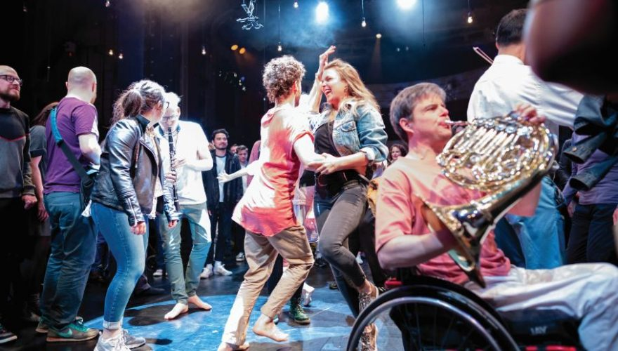 In the middle of a crowd sits a horn player in a wheel chair, behind him stands a clarinet player and two dancers are linking arms