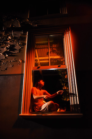 A woman sits in a window frame, in the dark.