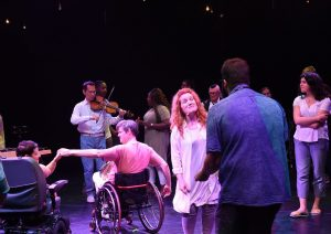Two people in wheelchairs entwine hands and a singer engages an audience member as dancers, musicians and audience mingle.