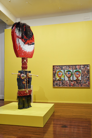 Foreground: brightly coloured idol, background: painting of child-like faces