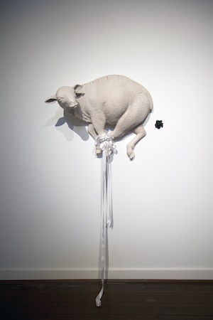 A wall sculpture of a lamb with its feet tied