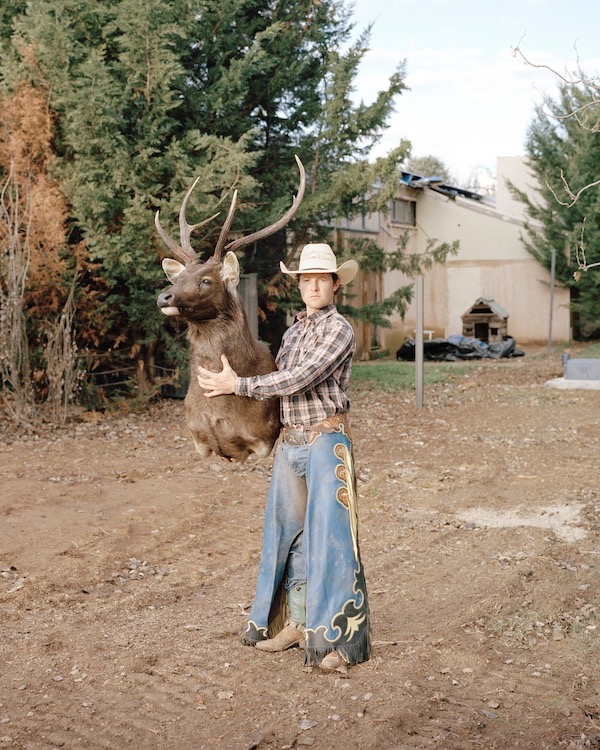 a cowboy holding a stuffed stag's head