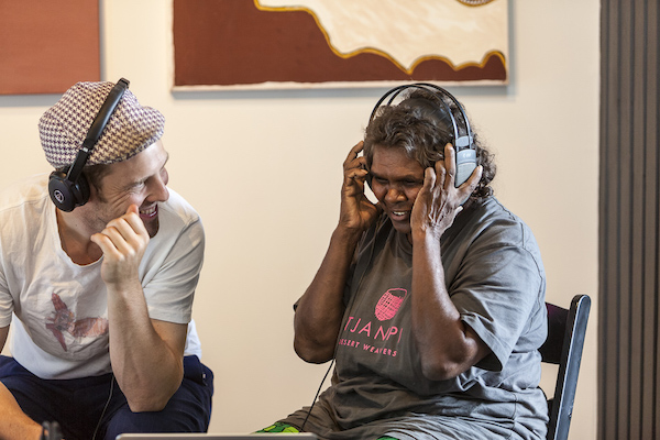 A man and a woman listening to headphones