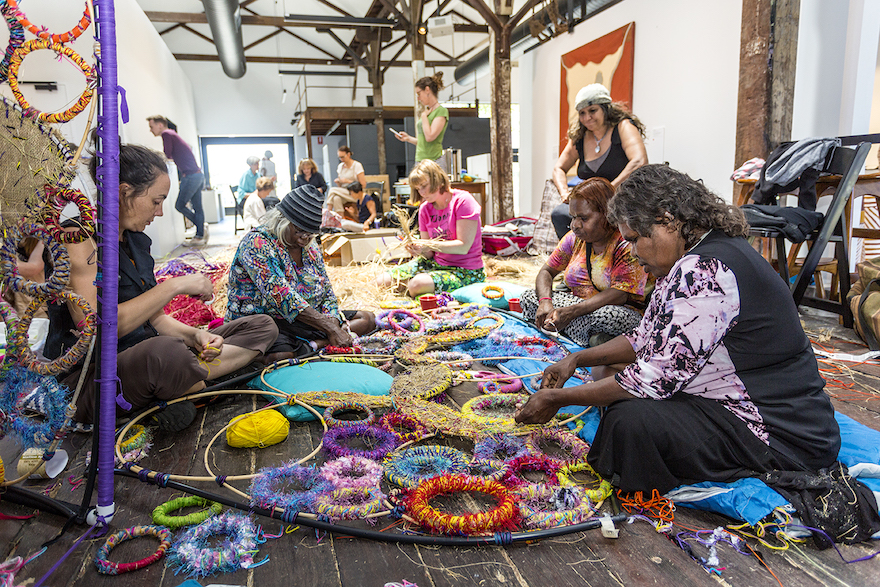 Women sitting in a circle, weaving colourful objects