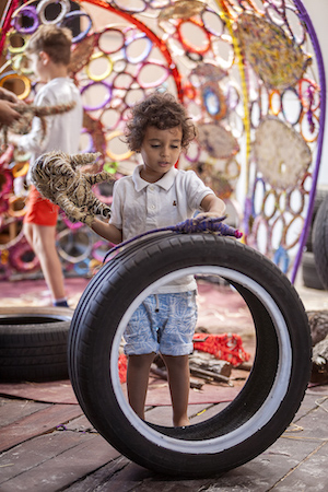A child, manipulating a tyre.