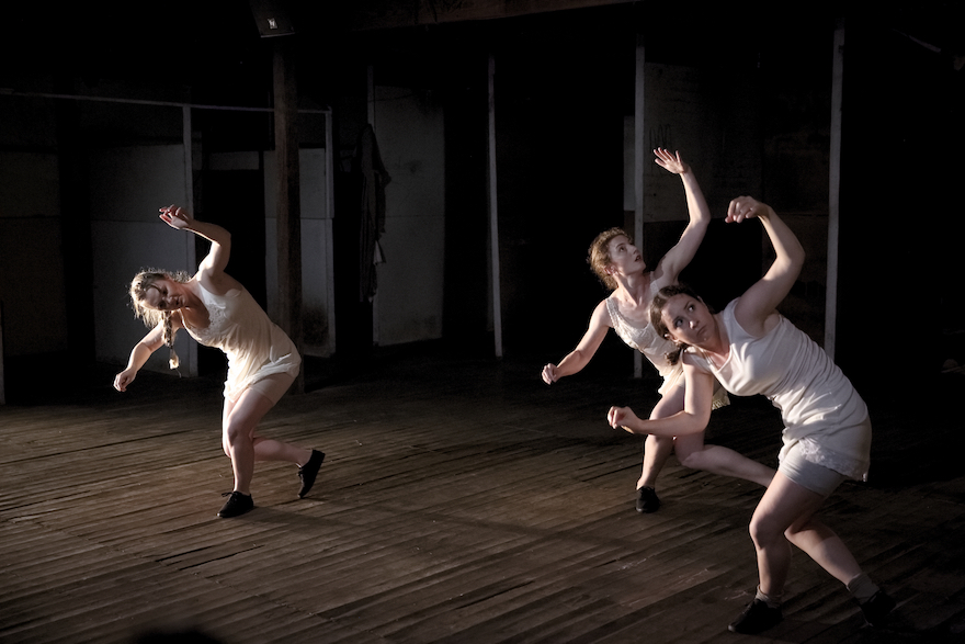 Three dancers in a shed, they each step one foot forward and spiral towards the front foot, arms held up as if in surrender.