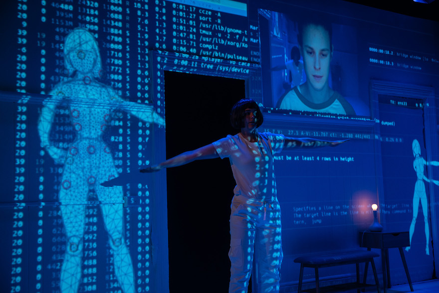 A performer stands, arms outstretched,  in front of projections of cyborgs and code, in 'The Double'.