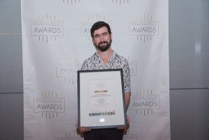 Scott McArdle holding his award