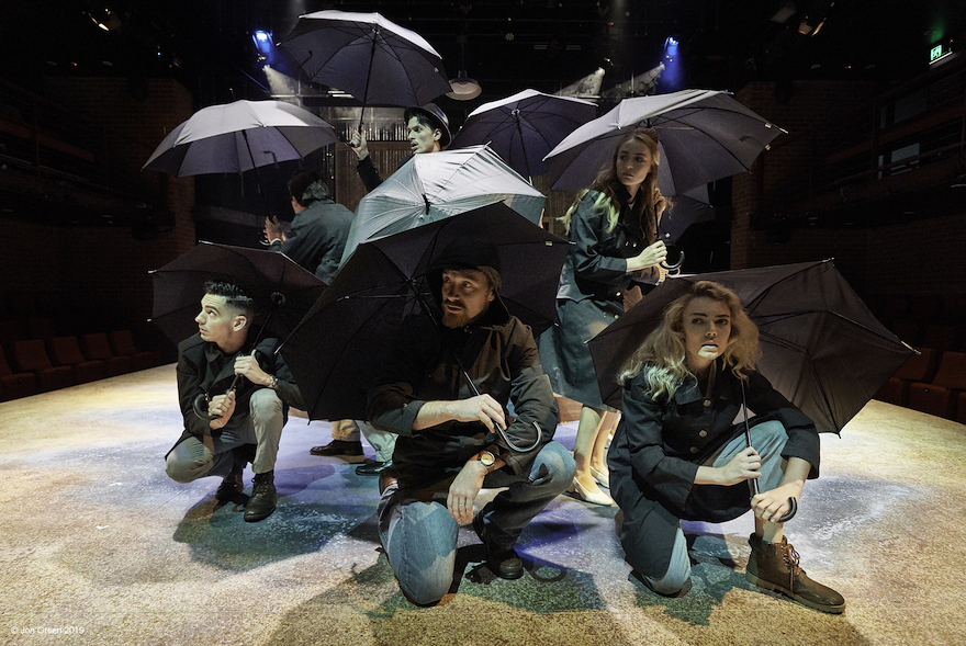 Performers on stage, crouched under umbrellas