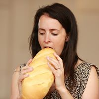 Laura Boynes eating a loaf of bread.