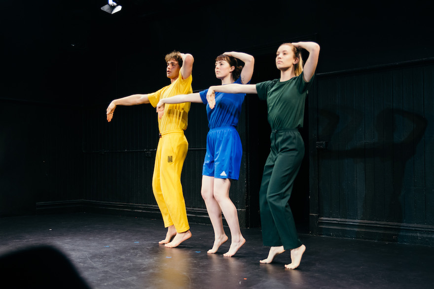 Three dancers: one in yellow, one in blue, one in green. Each has one arm over their head and other extended with a limp wrist.