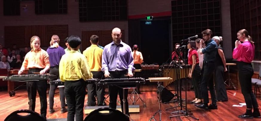 Percussionists playing marimba are joined by two piccolo players