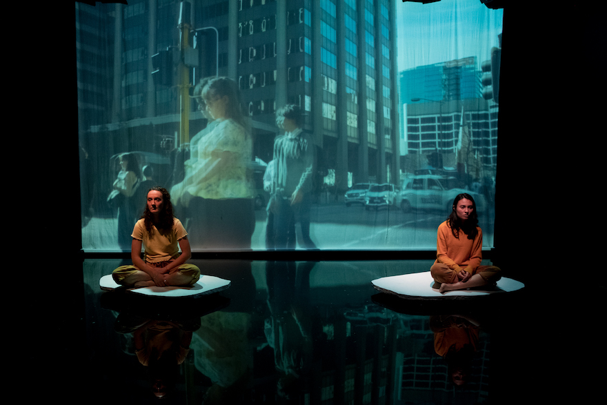 Two girls sit in front of a projected image of Perth CBD