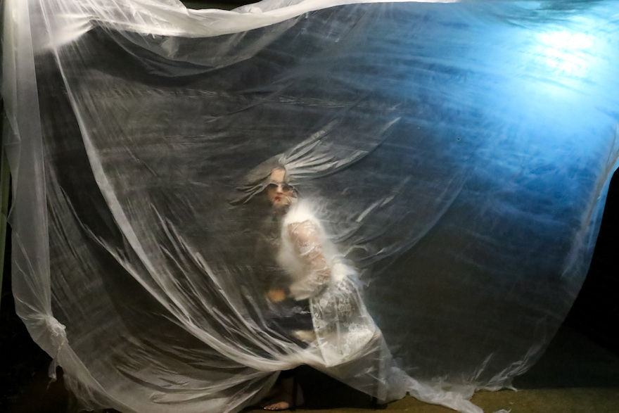 A dancer pressed up against a translucent sheet