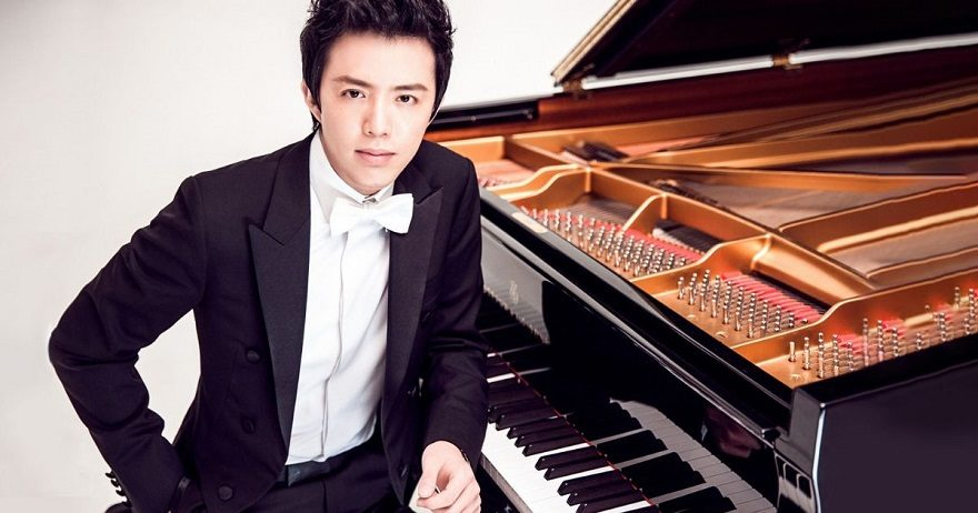 Man in dress suit sitting at grand piano