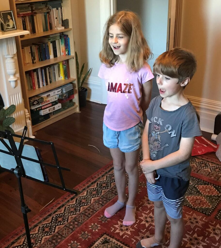 two children singing in their lounge