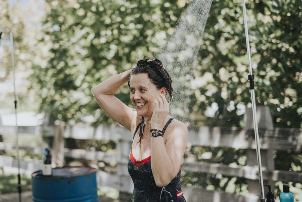 A woman having a shower outside. She is wearing black bathers and washing her hair. She is smiling and looks joyful.