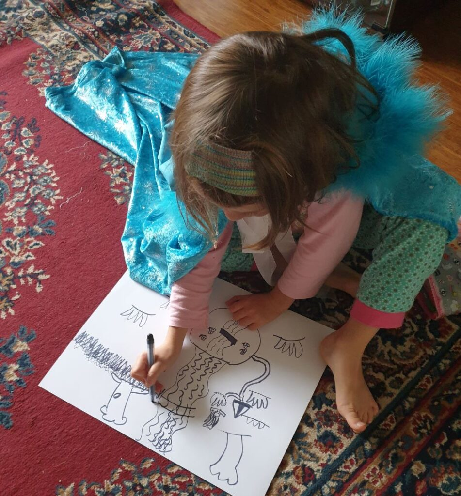 A child in a cape drawing a map
