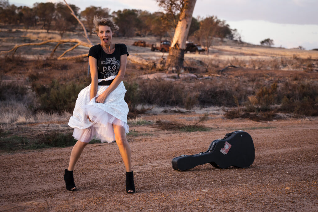 Alli Butler stands on a gravel road, with some cleared land, burnt out cars and bush in the background. She wears a Dolce and Gabbana t-shirt and a tutu skirt, with suede heels. A guitar case sits nearby.