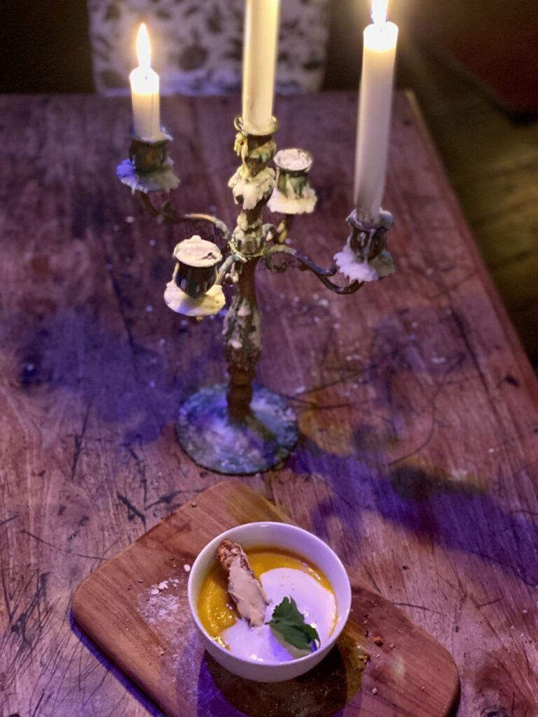 A bowl of pumpkin soup on a rustic board, with candelabra