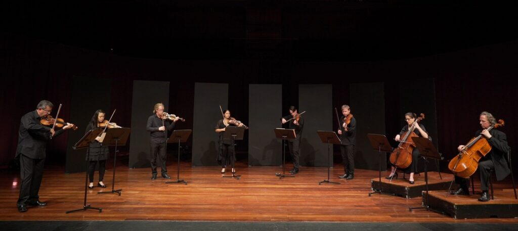 eight string players perform socially distanced on a stage.