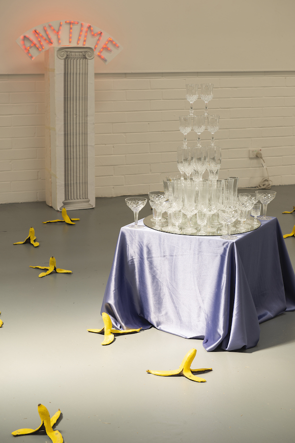 A table piled high with wine glasses, stacked in a pyramid. Around the table yellow banana skins dot the floor, their ends in the air and their peels spread like tripods.