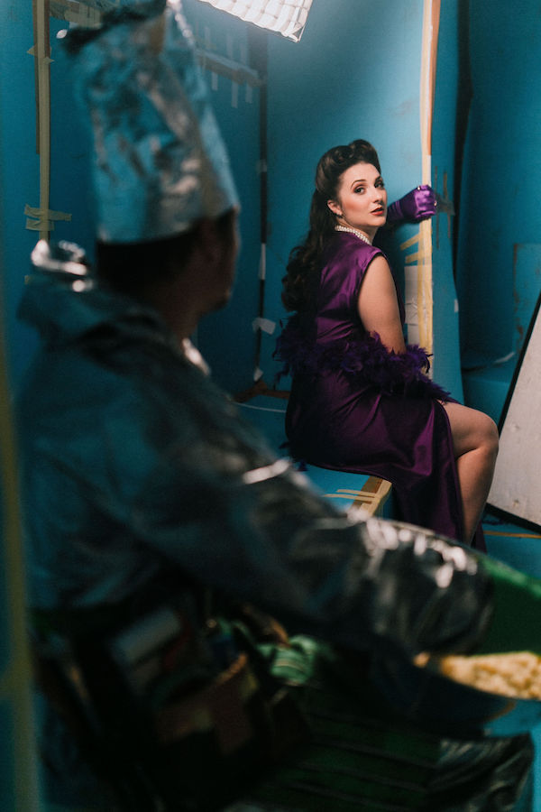 Chelsea Burns as Lucy. She wears a glamorous purple evening dress. She is seated and her body faces away from the camera, with her head twisting back over her shoulder to look at Ben whose outline we can see in the foreground.