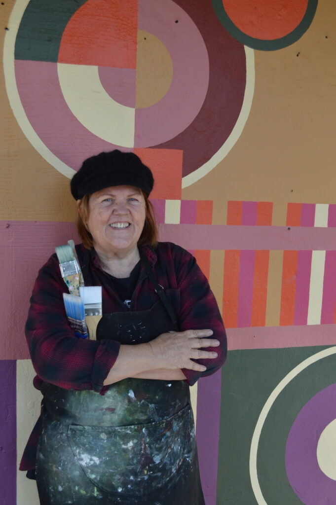 Gayle Mason stands outside her new gallery. She wears a black beret, a black and crimson checked shirt and an apron, spattered in paint. Her arms are crossed, clasping three paint brushes to her chest. The wall behind her is painted with abstract designs, circles and stripes in pinks, oranges and greens.