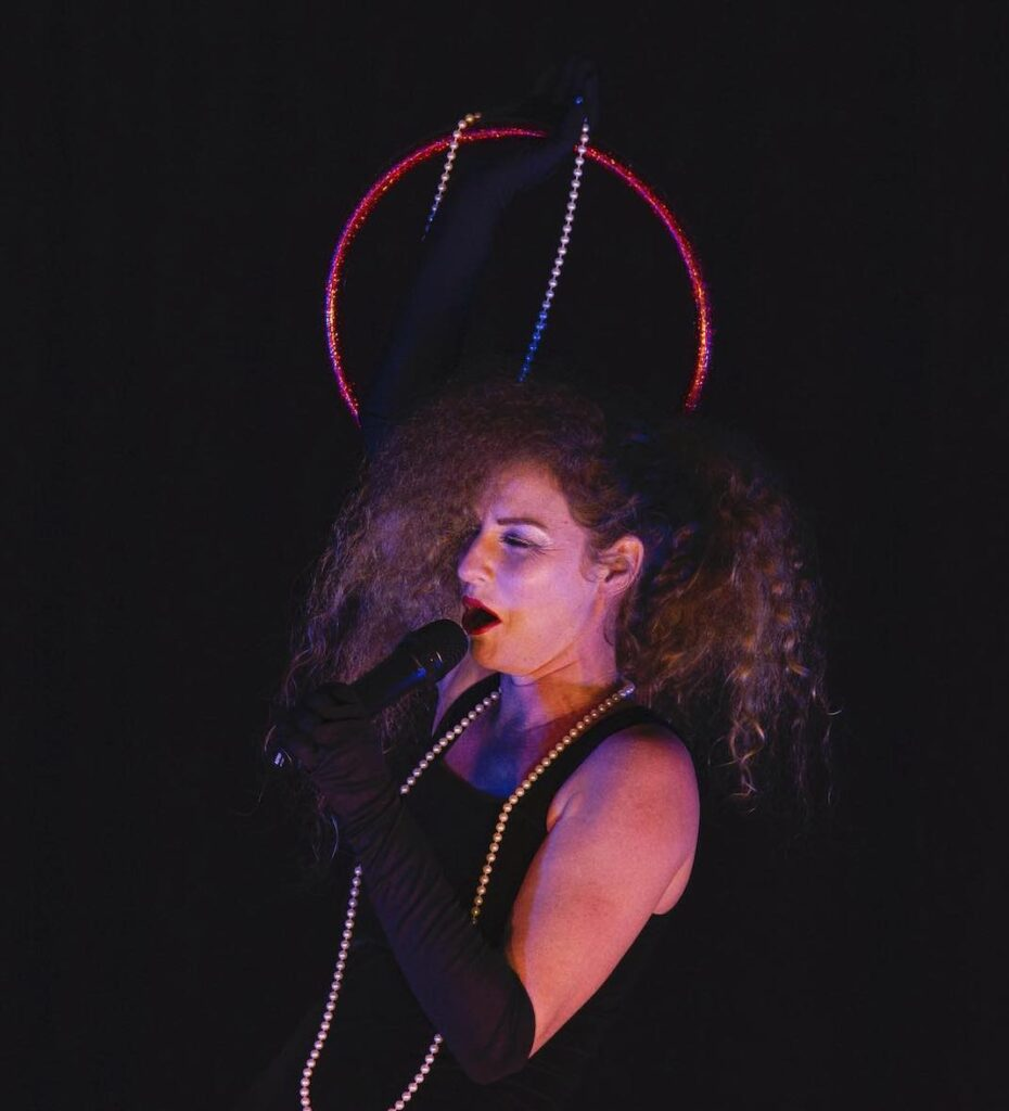 Ruth Battle sings. In one hand she holds a red glittered hoop and a string of pearls, in the other a mic. Her curly halr is teased and held off her face on one side. She wears a black pinafore dress, black gloves and a second string of pearls.