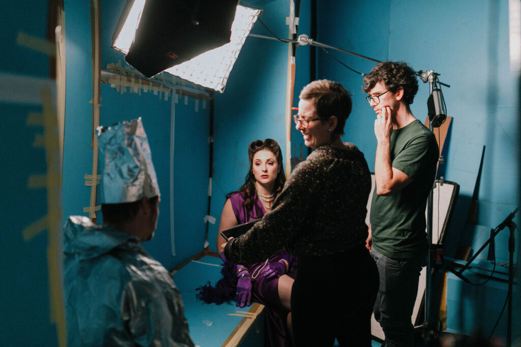Lachlann Lawton, Chelsea Kluga with Director Katt Osborne and Designer Tyler Hill on set. The set appears to be made of taped together blue cardboard.