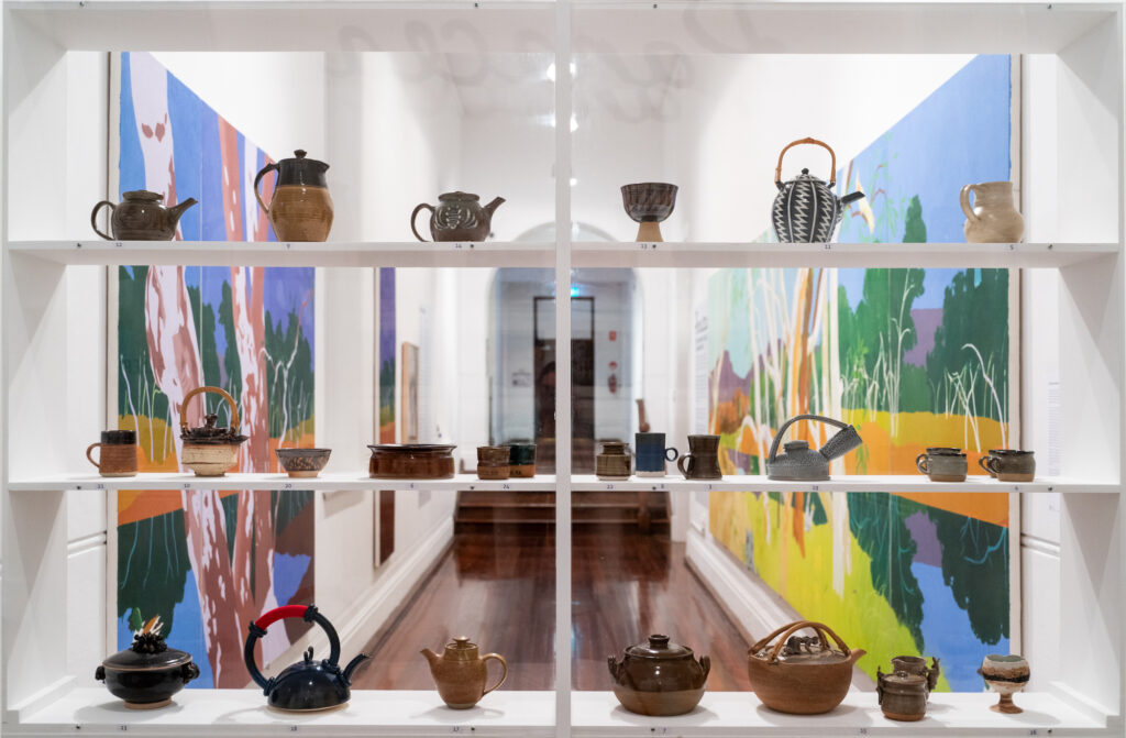 Through a glass display cabinet of teapots we can see brightly coloured paintings on either side of a corridor.