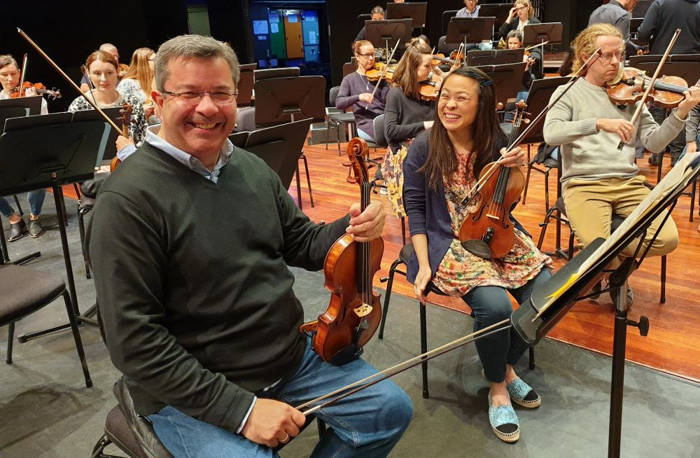 Two violin players wait for rehearsal to start with big smiles